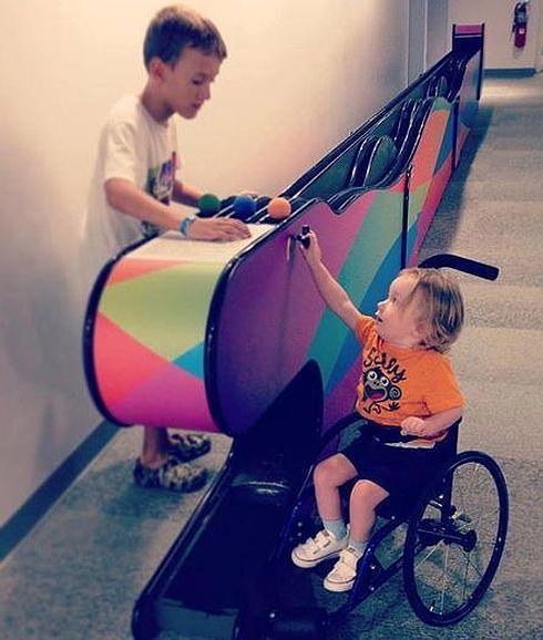 Un niño ayuda a Kaden a jugar en un museo de ciencias
